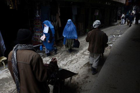 Afghan women and labourers with wheelbarrows walk down a lane in Kabul on Feb. 19, 2013.