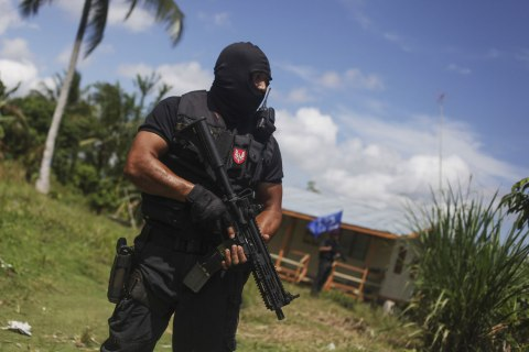 A member of the Malaysian Special Forces Unit stands guard as a standoff continues between the Malaysian police and an armed group of Filipinos in Kampung Senallang Lama, Malaysia, March 13, 2013.