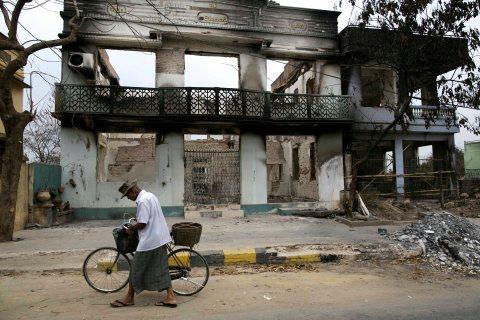A Burmese man walks by destroyed buildings on April 5, 2012 in Meiktila, Burma.