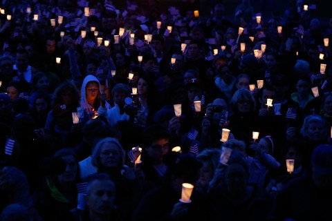 People gather with candles during a vigil for eight-year-old Martin Richard, from Dorchester, who was killed by an explosion near the finish line of the Boston Marathon on April 16, 2013 at Garvey Park in Boston, Mass.