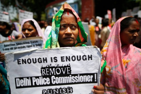 An Indian woman holds a poster as she protests
