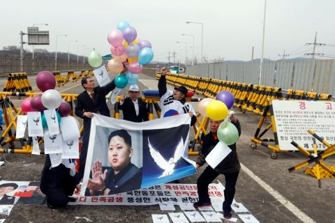 A group of anti-North Korean protesters release balloons with peace messages during a protest to denounce the North as they hold a placard showing a portrait of North Korean leader Kim Jong-Un in Paju.