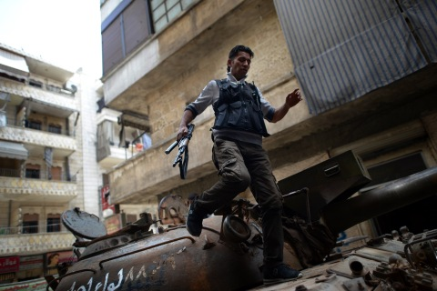 A Syrian rebel patrols an area in the Sheikh Maqsud district of the northern Syrian city of Aleppo, on April 11, 2013.