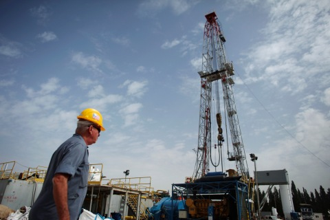 A worker walks near an oil rig belonging to Zion Oil and Gas in Karkur, in northern Israel, on Oct. 17, 2010.