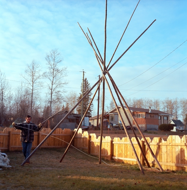 Norman Simpson puts up a teepee in his yard in preparation for the annual Christmas decoration competition in Fort McKay First Nation, Alberta.
