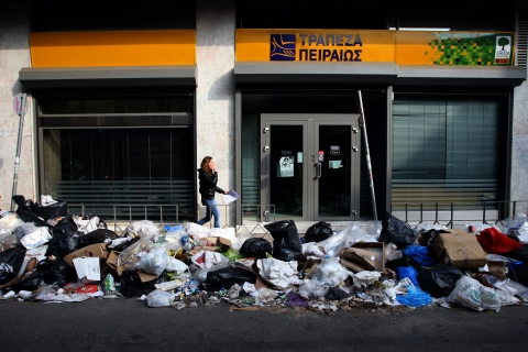 A woman walks by piles of garbage outside a bank branch in Thessaloniki, Greece, Nov. 27, 2012.