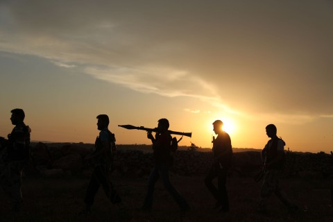 Syrian rebels walk to reposition near Mena airport, in Aleppo, Syria, on May 22, 2013.