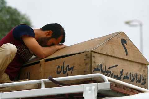 Ali Karim weeps over his daughter's coffin before her burial in the holy Shiite city of Najaf, south of Baghdad, Iraq, on May 20, 2013.