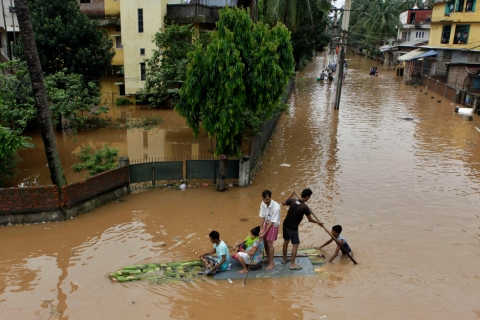 People use a raft made of banana plants to wade through flood waters in Gauhati, India, June 26, 2012.