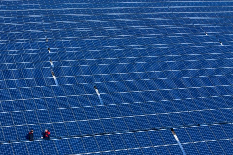 Two men stand in the new solar power plant of operating company Norddeutsche Energiegemeinschaft in Buetzow, Germany, March 15, 2013.