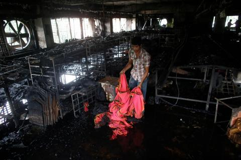 A garment worker inspects a factory after a fire in Dhaka.