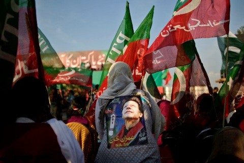 Pakistani supporters of former cricket star-turned-politician, and leader of Pakistan Tehreek-e-Insaf party, Imran Khan, wave his party's flag during a rally in Islamabad, May 9, 2013.