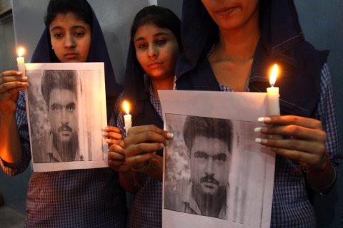 Indian school children pay tributes holding portraits of Indian prisoner Sarabjit Singh