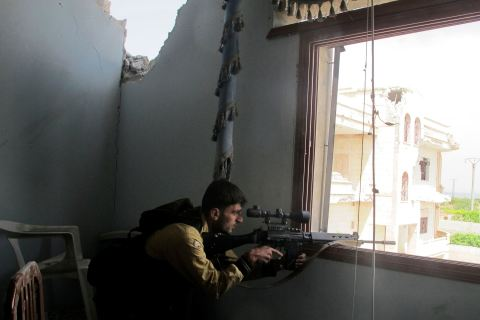 A Free Syrian Army sniper takes position in a damaged house in Idlib