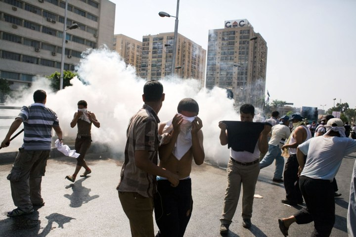 Egyptian protesters take cover from tear gas during clashes next to the headquarters of the Republican Guard, in Cairo, on July 5, 2013.