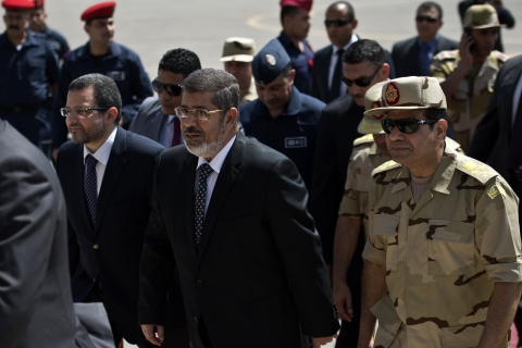 From left: Egyptian Prime Minister Hisham Qandil, President Mohamed Morsi, and Defense Minister Abdelfatah al-Sissi arrive at Almaza military Airbase in Cairo on May 22, 2013 to attend the welcoming of the policemen and soldiers who were seized in Sinai by kidnappers following their release.
