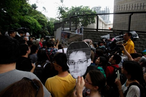 A protester carries a paper cutout of Edward Snowden, a former contractor at the National Security Agency, during a demonstration outside the U.S. Consulate in Hong Kong on June 15, 2013.