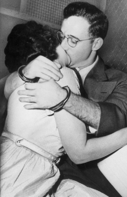 Married American traitors Julius and Ethel Rosenberg, wearing handcuffs, kiss in the back of a prison van after their treason arraignment, in New York, September 1950.