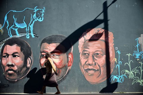 A woman walks past a mural portraying former South African President Nelson Mandela in downtown Johannesburg, on June 11, 2013.
