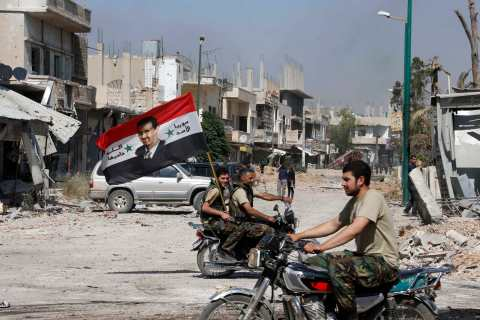 Forces loyal to Syria's President Assad carry the national flag as they ride on motorcycles in Qusair