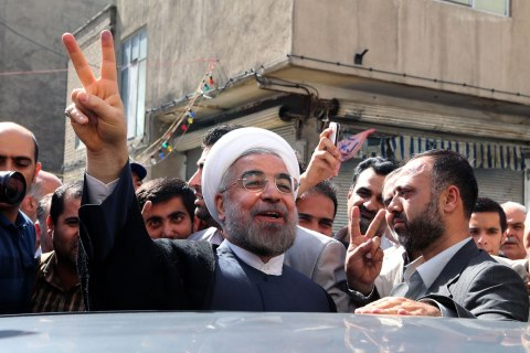 Iranian moderate presidential candidate, Hassan Rowhani flashes the sign of victory as he leaves a polling station after voting on June 14, 2013 in Tehran.