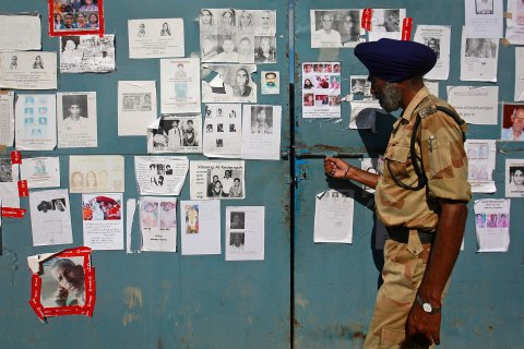 A security personal opens a gate covered in posters of missing people, affected by the flash floods and landslides, at the Indian Air Force base in Dehradun