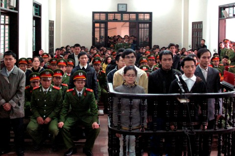 Defendants stand in front of dock at a court in Nghe An province, south of Hanoi
