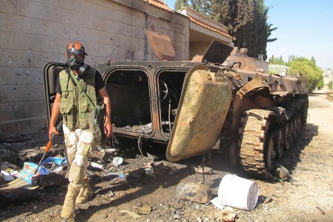 A Free Syrian Army fighter wearing a gas mask, carries his weapons as he walks past a damaged tank, after seizing a government military camp used by forces loyal to Syria's President Bashar al-Assad, near Idlib