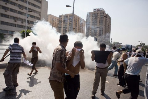 Egyptian protesters take cover from tear gas during clashes next the headquarters of the Republican Guard, in Cairo, Egypt, 05 July 2013.
