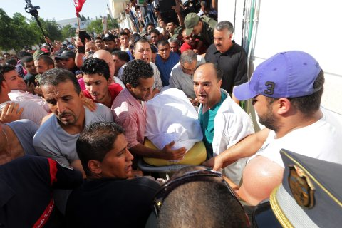 Tunisian medics carry the body of slain opposition politician Mohamed Brahmi, as protesters gather at the hospital in Tunis, Tunisia, on July 25, 2013.