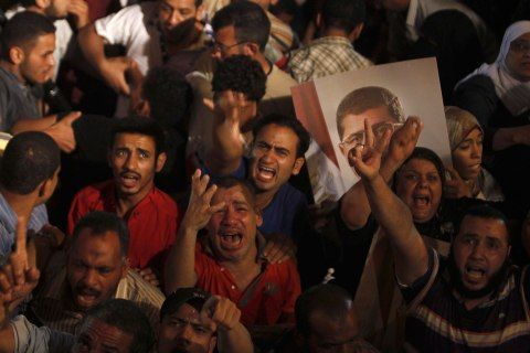 Supporters of Egypt's President Mohamed Mursi react after the Egyptian army's statement was read out on state TV, at the Raba El-Adwyia mosque square in Cairo