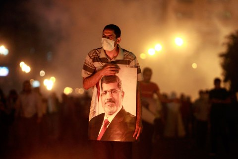 An injured supporter of deposed Egyptian President Mohamed Morsi carries a poster of Morsi as they run from tear gas fired by riot police during clashes on the Sixth of October Bridge over the Ramsis square area in central Cairo, July 15, 2013