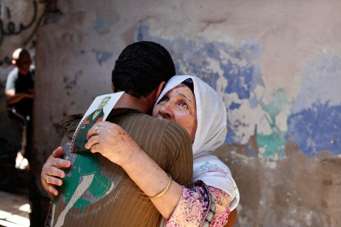 The mother of Palestinian Ateya Abu Moussa, who has been held prisoner by Israel for 20 years, reacts as she is hugged by her grandson after hearing news on the possible release of her son, in Khan Younis in the southern Gaza Strip July 28, 2013.