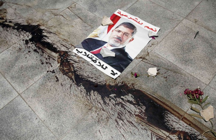 The blood from members of Muslim Brotherhood and supporters of deposed President Mursi, killed during late night clashes, stain floor near a poster of Mursi at Tomb of the Unknown Soldier in Nasr city
