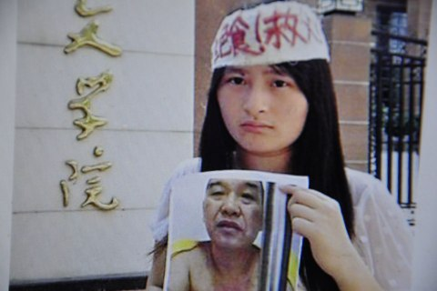 Zeng Shan, the daughter of Chinese businessman Zeng Chengjie, holds a picture of her father, in Changsha, China, on July 7, 2013.