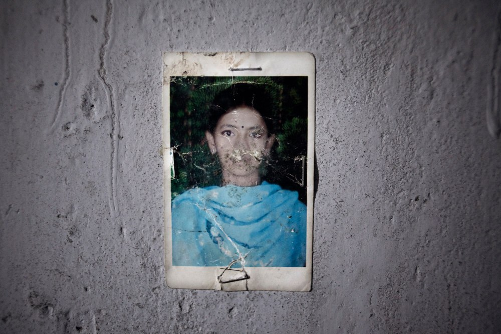 After Shanta's father died, she became her family's sole breadwinner, supporting her mother and younger brother with her wages from the garment factory. Her mother, Shahida, does not know the name of the factory where she worked and has begun selling their furniture to pay the rent on their home, where Shanta's photo is proudly displayed.
