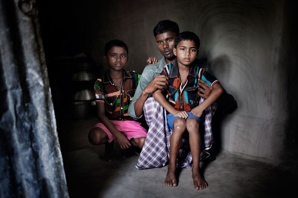 Missing workers Rehana's two son Parvej (7) and  Palash (5) and her husband Jahedul at their home district Joypur hat. Rehana  is missing after the Rana plaza collapse. Rehana was a helper of New Wave Style Garment. After Rahana's missing news her son's become so quite. All the time they ask many questions to their father ,Jahidul, about their mother and waiting for mother. Rana Plaza, the 8- stored building where 5 garment factory were running, has collapsed on 24th April 2013 and 1131 workers dead so far. Panch bibi, Joypur Hat, Bangladesh. 2nd June 2013
