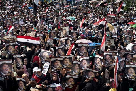 Egyptian supporters of deposed president Mohamed Morsi wave their national flag as they attend a rally in support of the former Islamist leader outside Rabaa al-Adawiya mosque in Cairo, on July 8, 2013.