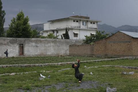 A young boy plays with a tennis ball in front of the compound where U.S. Navy SEAL commandos reportedly killed al Qaeda leader Osama bin Laden in Abbottabad, on May 5, 2011.