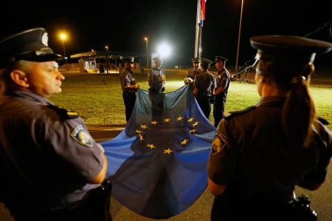 Croatian policemen prepare to raise the EU flag for the first time at the Bajakovo border crossing between Serbia and Croatia
