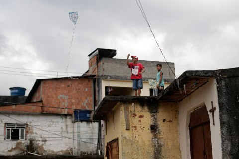 A boy flies a kite on the roof of the Chapel of Sao Sebastiao, where Pope Francis is expected to visit during his upcoming trip to Varginha slum in Manguinhos slums complex in Rio de Janeiro July 16, 2013