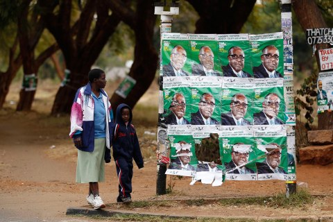 A woman and a child walk past election posters of Zimbabwe's President Robert Mugabe in Harare on July 30, 2013.