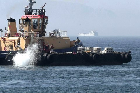 Workers throw concrete blocks from a Gibraltar tug into the sea in an area where Spanish fishing boats usually sail around off Gibraltar's coast, on July 25, 2013.