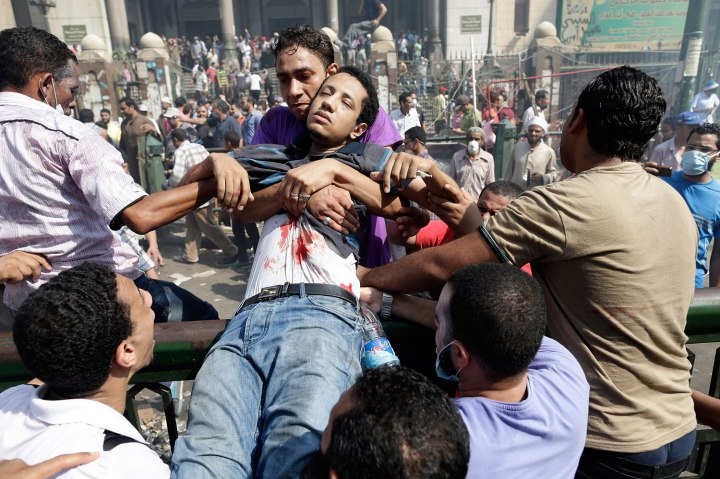 Supporters of Egypt's ousted President Mohammed Morsi carry a wounded man during clashes with Egyptian security forces in Ramses Square, downtown Cairo, Egypt, Friday, Aug. 16, 2013.