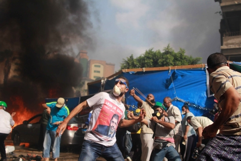 Supporters of the Muslim Brotherhood and Egypt's ousted president Mohamed Morsi throw stones during clashes with security forces in Cairo, on Aug. 14, 2013, as security forces backed by bulldozers moved in on two huge pro-Morsi protest camps.