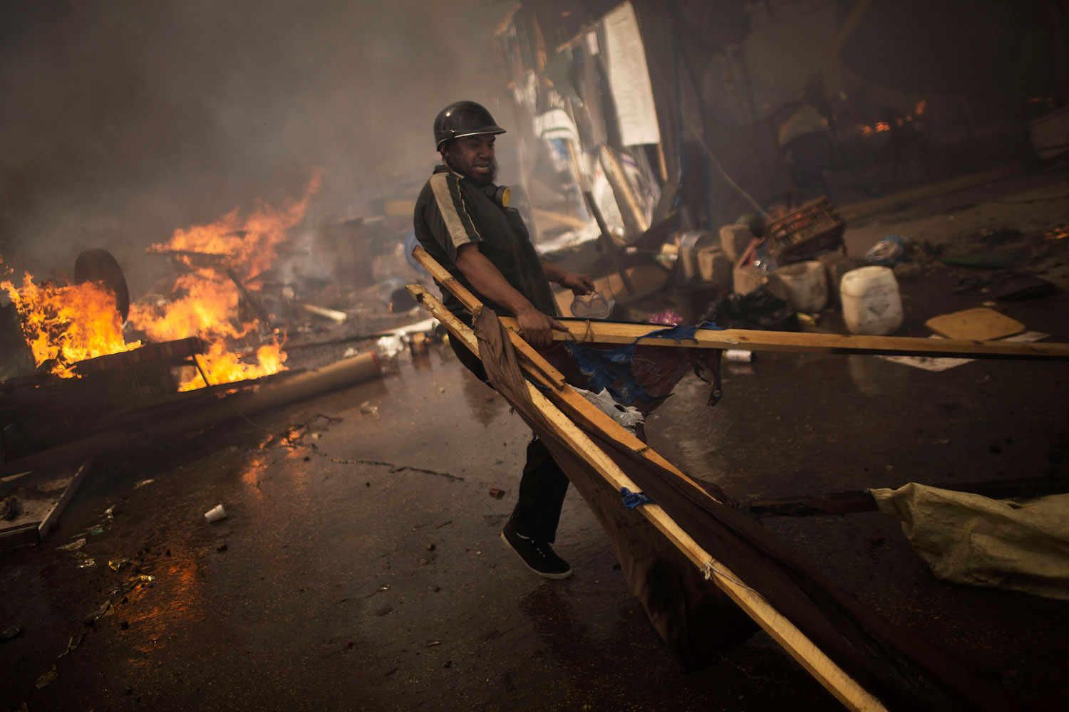 A supporter of ousted Islamist President Mohammed Morsi carries woods to burn in a fire barricade at the sit-in at Rabaa Al-Adawiya square in Cairo's Nasr City district, Aug. 14, 2013.