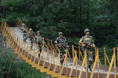 Indian BSF soldiers patrol over a footbridge built over a stream near LoC, a ceasefire line dividing Kashmir between India and Pakistan, at Sabjiyan sector of Poonch district