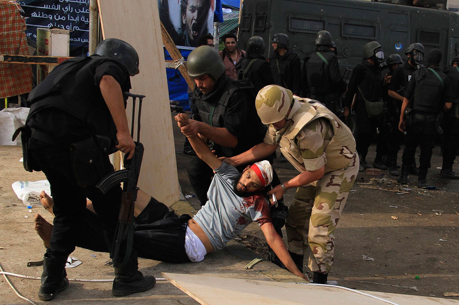 An injured member of the Muslim Brotherhood and supporter of deposed Egyptian President Mohamed Mursi is carried by members of the riot police and the army after they cleared Rabaa Adawiya square area, where the Pro-Mursi supporters are camping, in Cairo