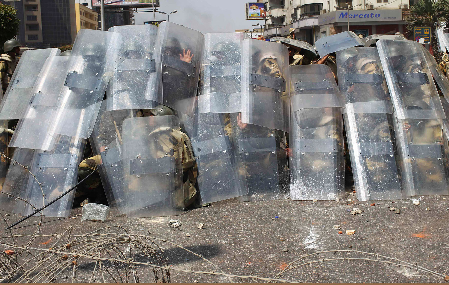Riot police and army soldiers protect themselves with riot shields as members of the Muslim Brotherhood and supporters of ousted Egyptian President Mohamed Mursi throw stones during clashes around the area of Rabaa Adawiya square, where they are camping, in Cairo, Aug. 14, 2013.