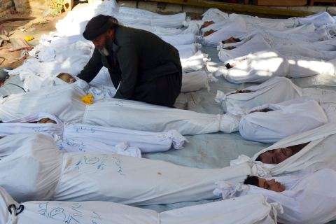 A man holds the body of a dead child among bodies of people activists say were killed by nerve gas in the Ghouta region, in the Duma neighbourhood of Damascus, on Aug. 21, 2013.